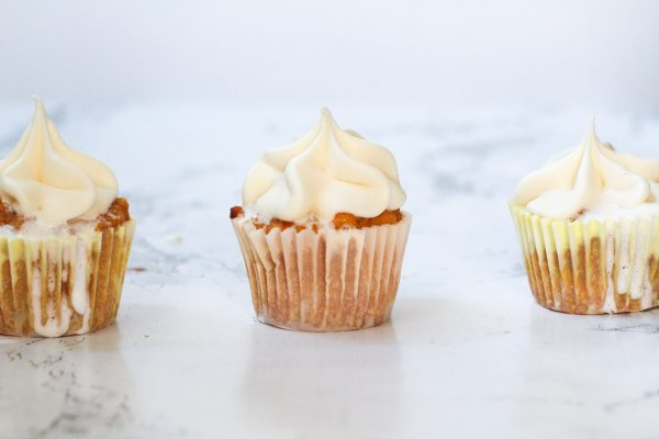 four sweet potato fluff cupcakes lined up horizontally across the image, on a white marbled surface, with a greyish white background