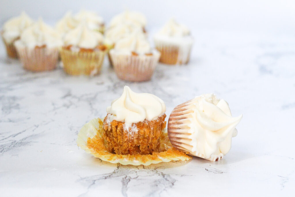 a sweet potato fluff cupcakes with the paper liner pulled down with a sweet potato cupcake in its liner on it's side leaning up against the one with the liner pulled down. A group of more cupcakes are behind them in the upper left corner of the photo.  All on a marbled white surface.