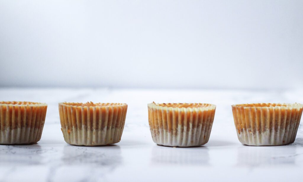 side view of 4 pumpkin pie cheesecakes in a horizontal line in paper wrappers on a white marble surface
