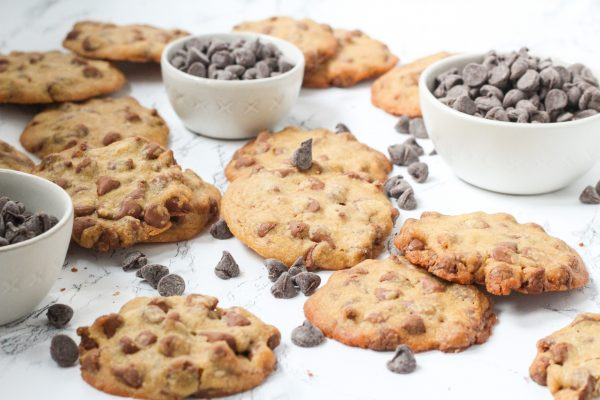 Angled view of a lot of cookies with three small bowls of chocolate chips and loose chocolate chips spread around throughout the cookies
