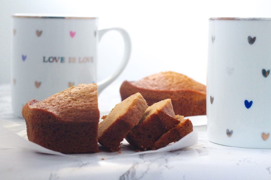 Side view of a partially sliced chai loaf with a whole chai loaf in the background. Behind the sliced chai loaf toward the left is a white mug with colorful hearts that says love is love, and next to the sliced chai loaf to the right, cut off in the frame, is a matching mug, but without the words