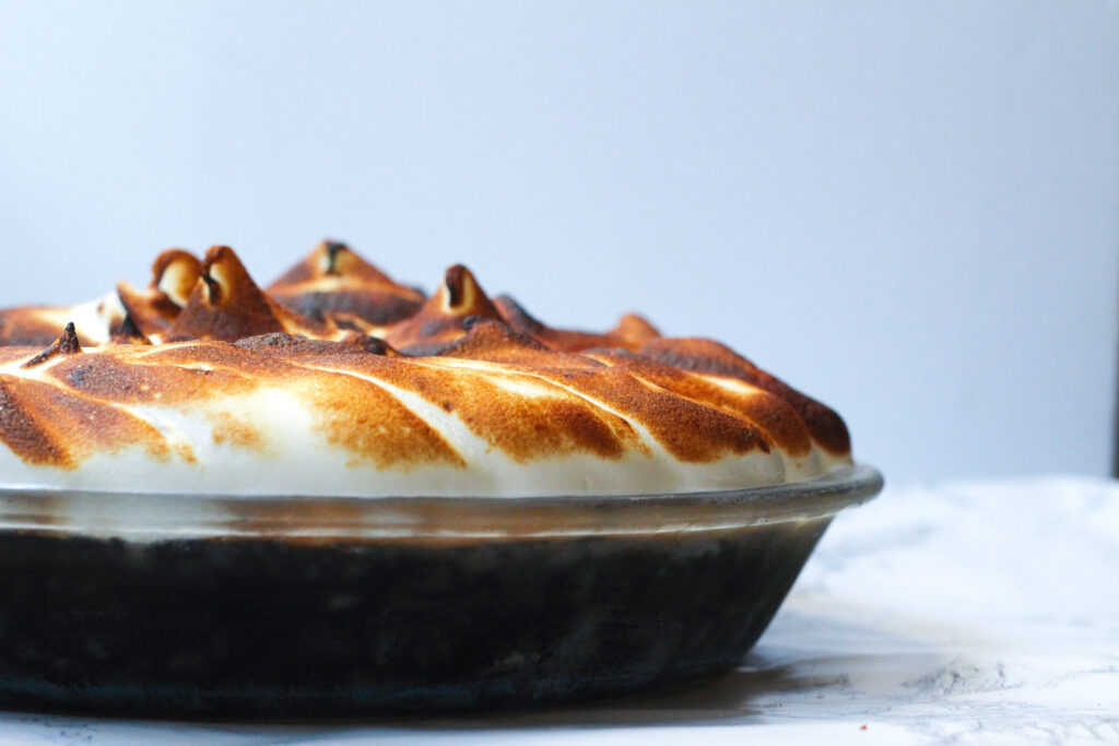 Side view of a mocha meringue pie, cutting out of frame on the left side of the image