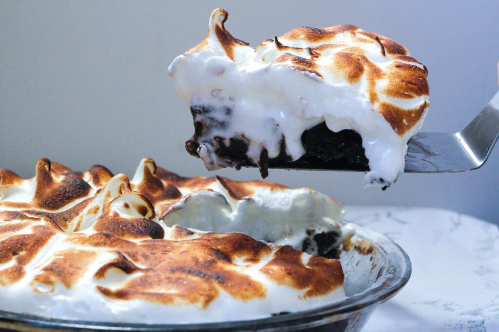 Side view of a mocha meringue pie on the left, with a single slice being lifted out on a pie server on the right