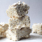 A stack of 3 maple rice krispie treats on a white marbled surface in front of a grey background and a few more maple rice krispie treats in a single layer