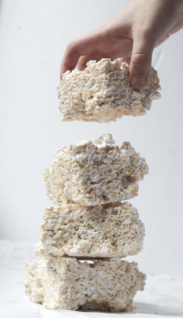 A hand placing a fourth rice krispie treat on a stack of three maple rice krispie treats in front of a white background
