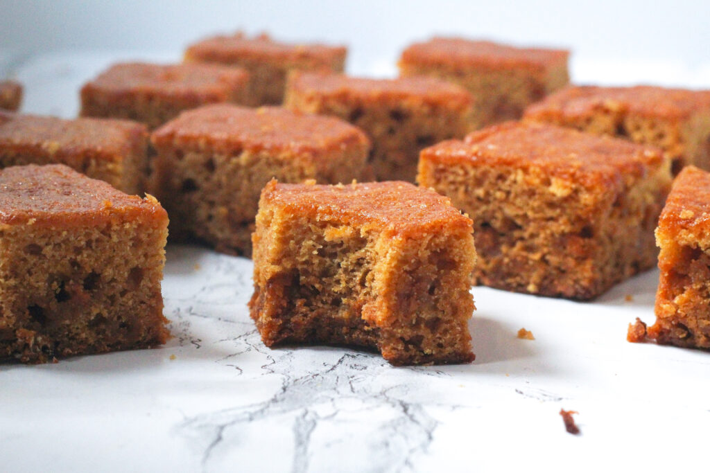 Side view of a bunch of butterscotch blondies on a white marble surface, with a front and fairly central one having a bite taken out of it