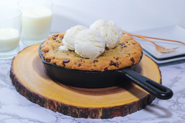 cast iron cookie topped with three scoops of vanilla ice cream in the skillet on a round piece of wood with two glasses of milk in the top left corner, one full and one less than half full, and two square white plates in the top right corner with two rose gold forks on them, all on a marbled surface