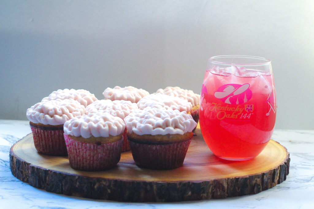 Lily Cupcakes on a round piece of wood with an Oaks Lily to the right in a stemless Oaks Day wine glass
