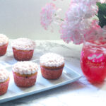 three lily cupcakes on a rectangle plate with more lily cupcakes behind the plate on the left side of the frame. An Oaks Lily in a stemless Oaks Day wineglass with pink and white flowers in the background