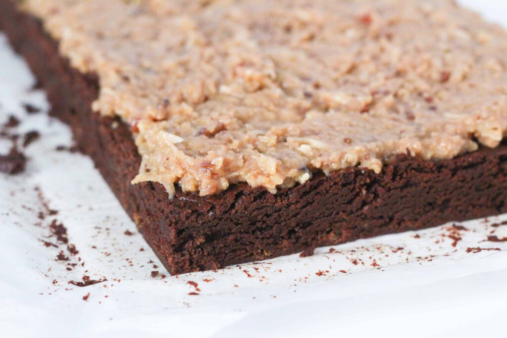 Close up angled view of the corner of a batch of german chocolate brownies before the brownies have been sliced.