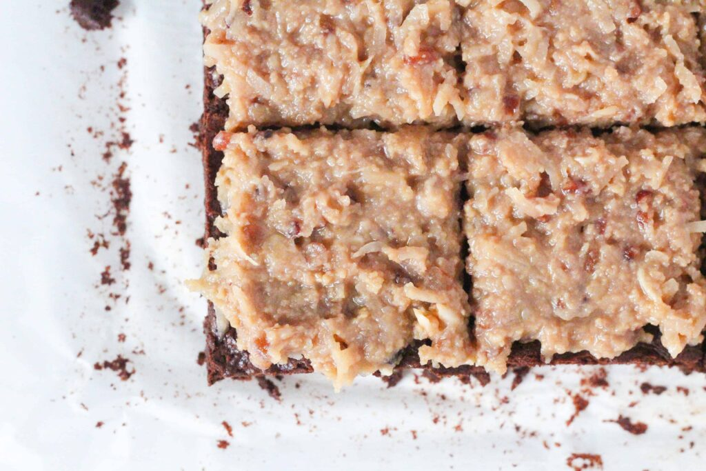 top down view of the corner of a batch of german chocolate brownies topped with a traditional coconut pecan frosting. The brownies are sliced into squares. The bottom left brownie is the only one fully in the shot, and the brownie above it, to the upper right, and to the right are all partially in frame.