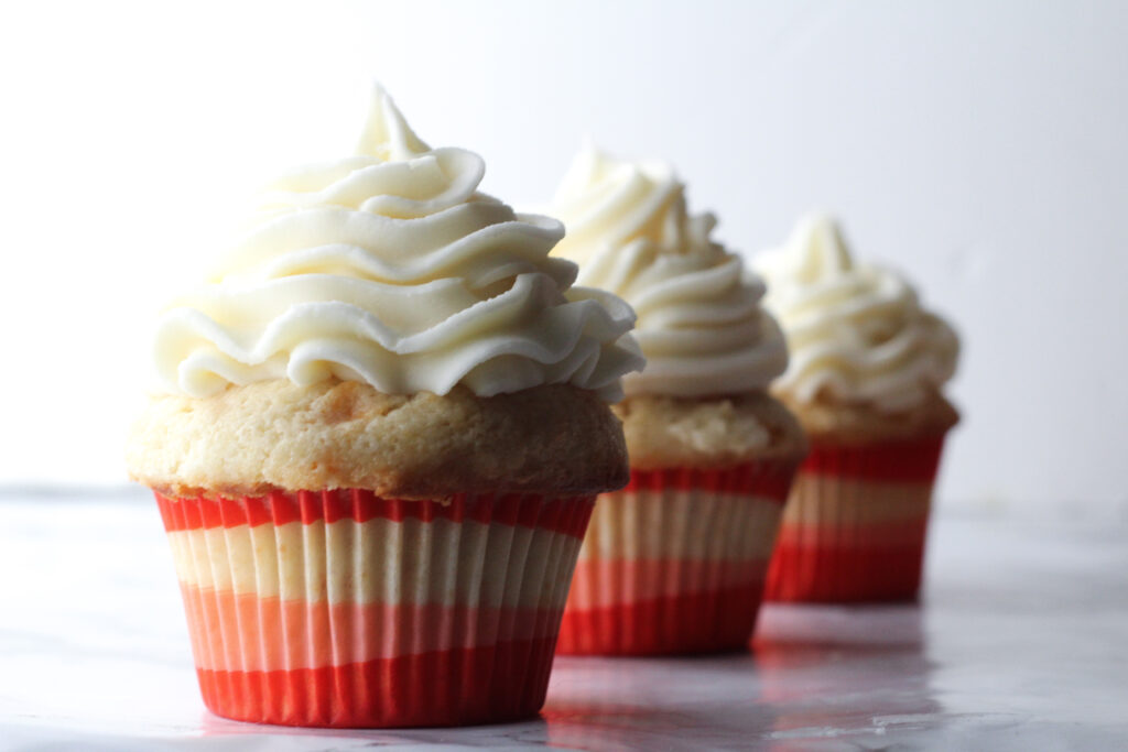 three bourbon peach sweet tea cupcakes in a diagonal line in red, white, and pink wrappers on a marbled surface in front of a white background