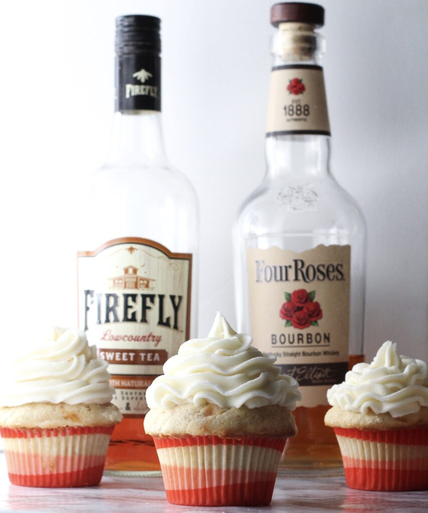 three bourbon peach sweet tea cupcakes in front of a bottle of firefly sweet tea vodka and a bottle of four roses bourbon
