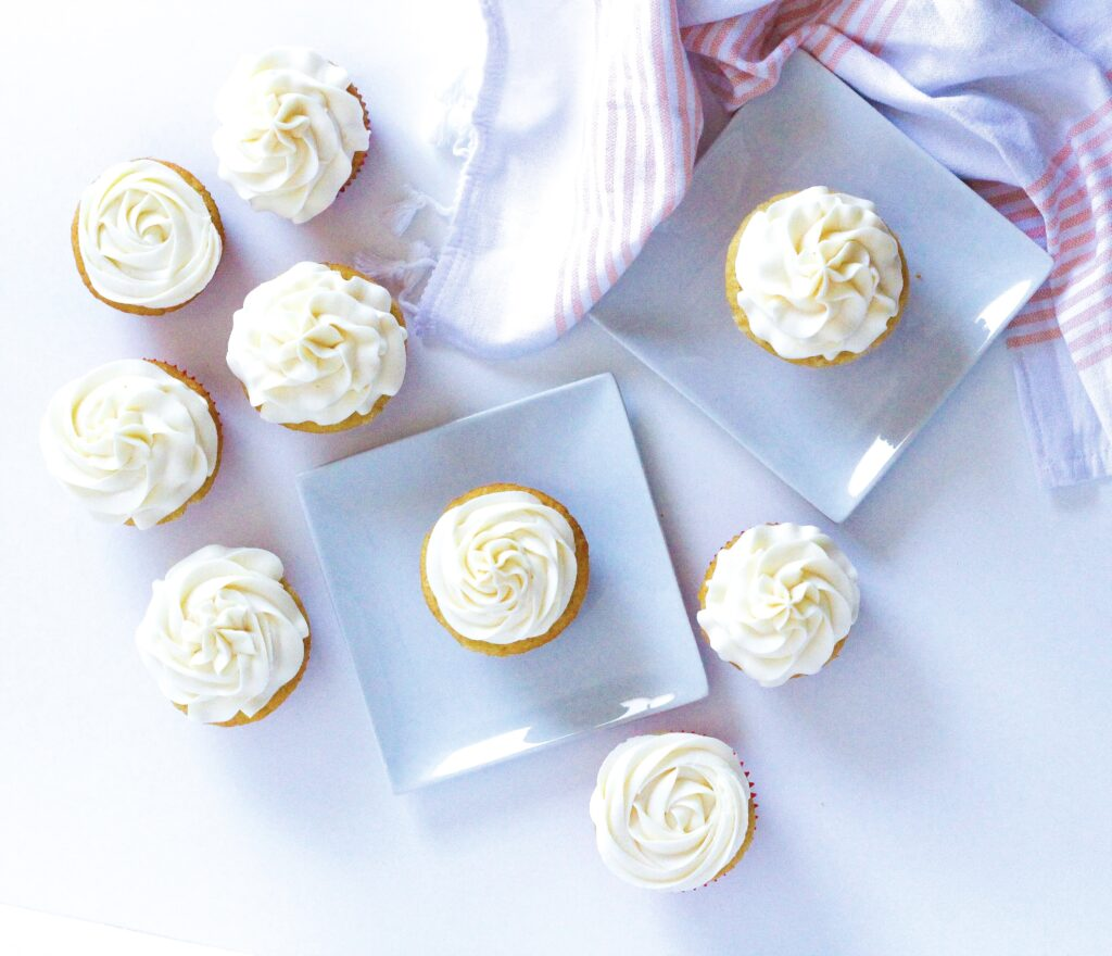 top down view of wannamango cupcakes on a white surface, each of two cupcakes are on square white plate. In the top right corner of the frame is a white and peach colored cloth napkin.