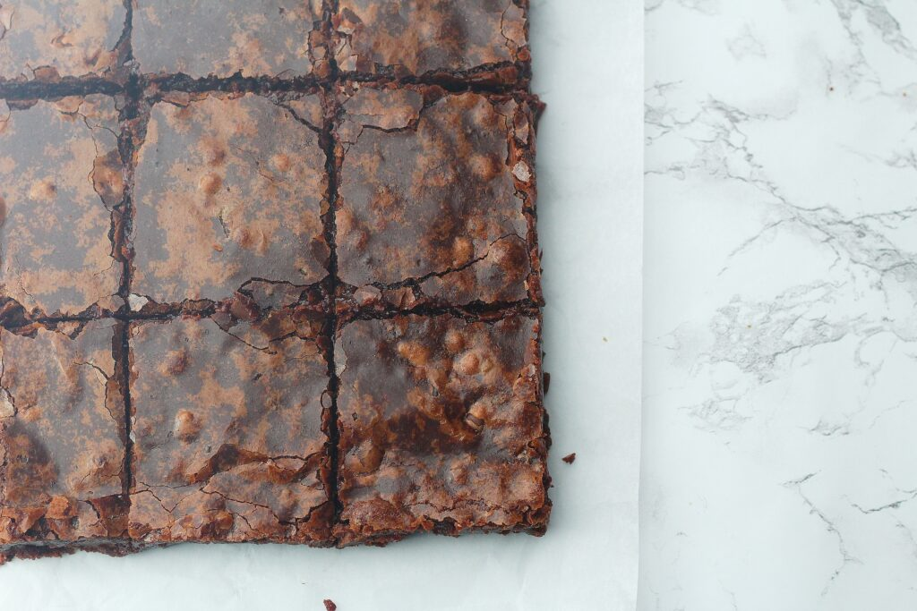 Top view of fudgy brownies on the parchment paper on top of a marble surface