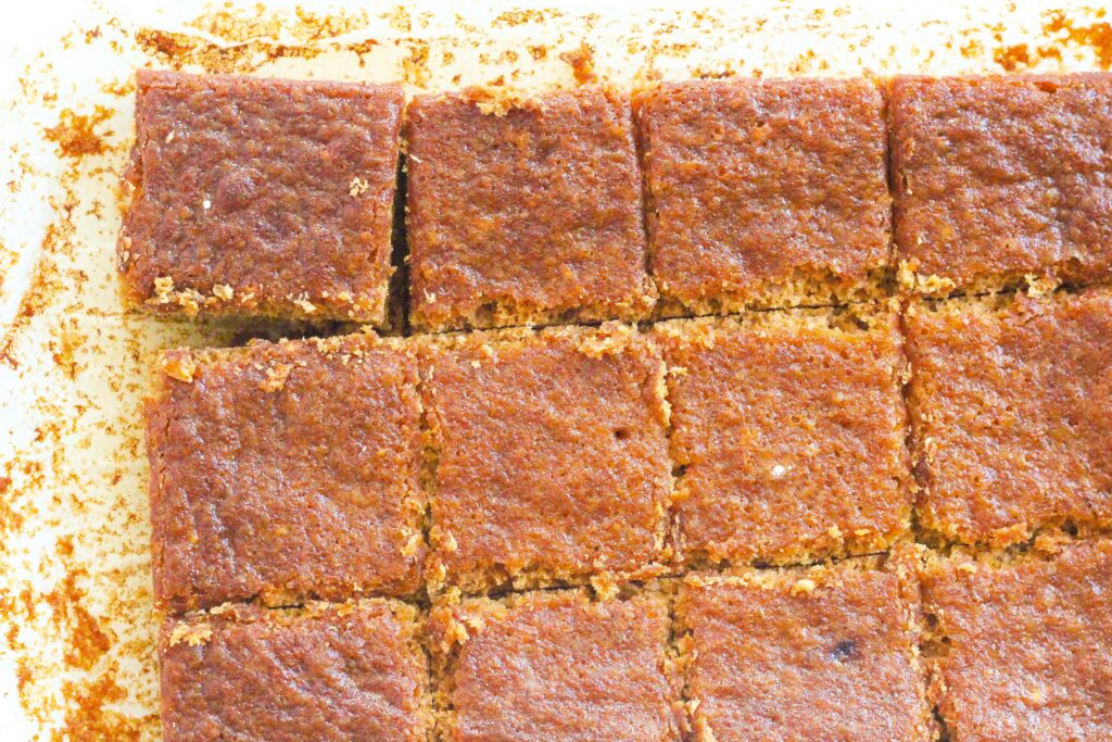 top down view of salted caramel maple bars sliced into squares, going out of the frame to the bottom right. The top left square is slightly tiled out of line.