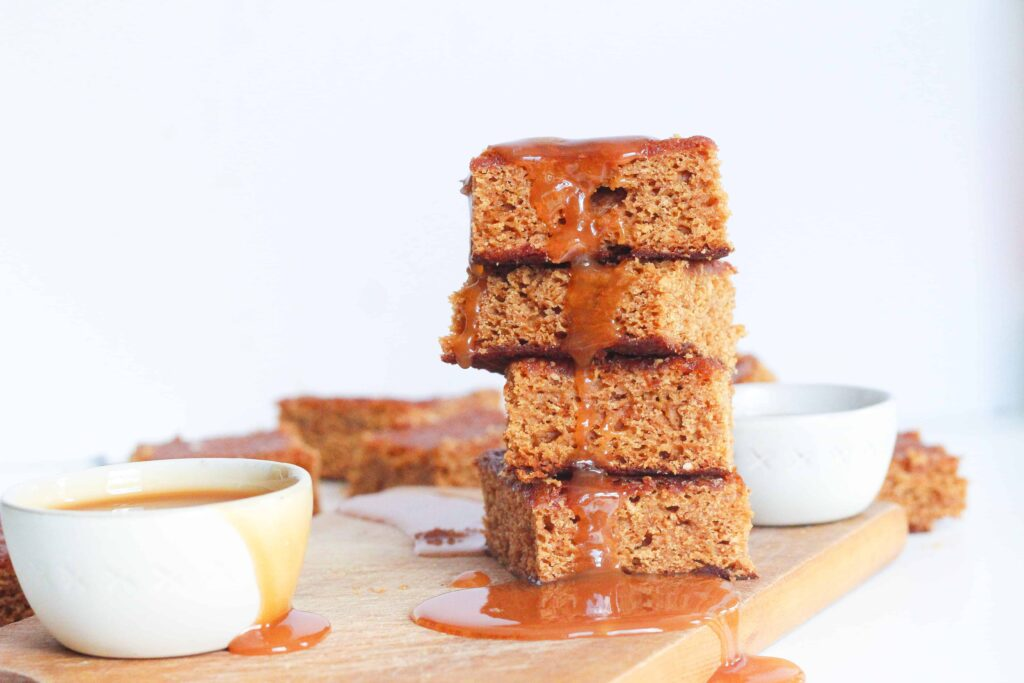 side view of a stack of four salted caramel maple bars with caramel dripping down the side