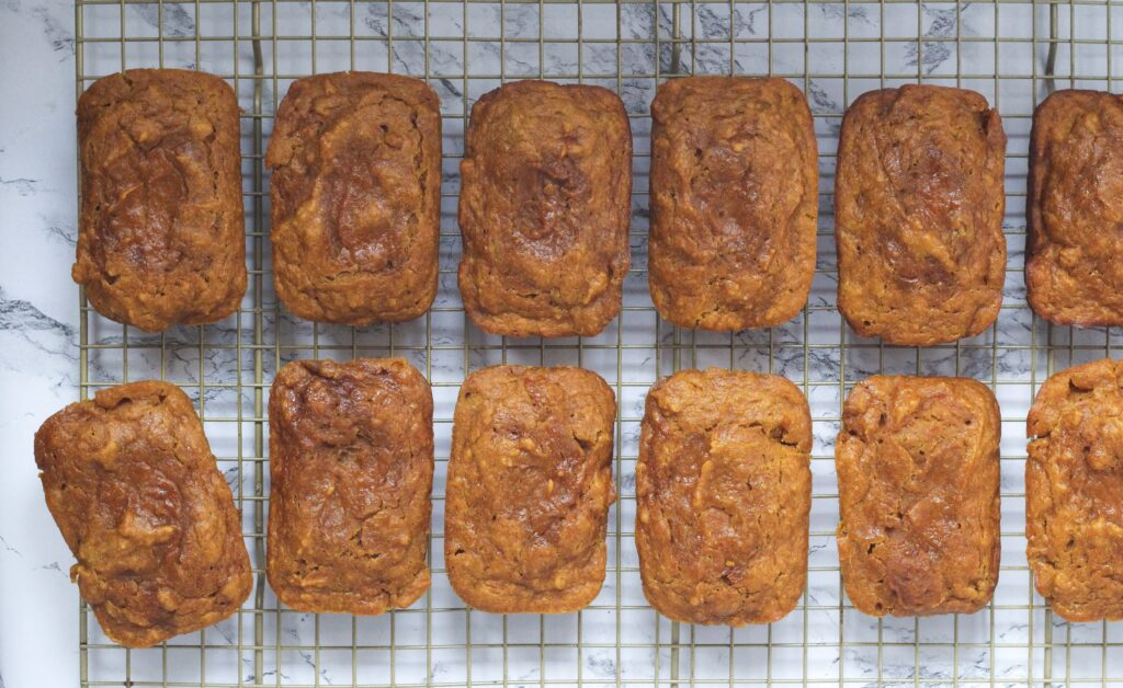 top down view of two horizontal rows of mini pumpkin chai breads, with each mini loaf laying vertically. The loaves are on a wire rack, and the bottom left roll is slightly tilted out of line
