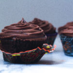 Side view of a fiery chocolate cupcake with it's halloween cupcake wrapper peeled down and a few cupcakes in the background