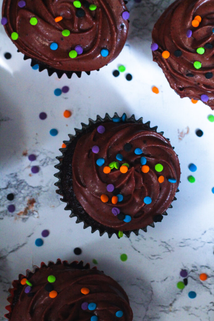 Top down view of fiery chocolate cupcakes with blue, purple, orange, and green confetti sprinkles on top, and on the white marbled surface underneath