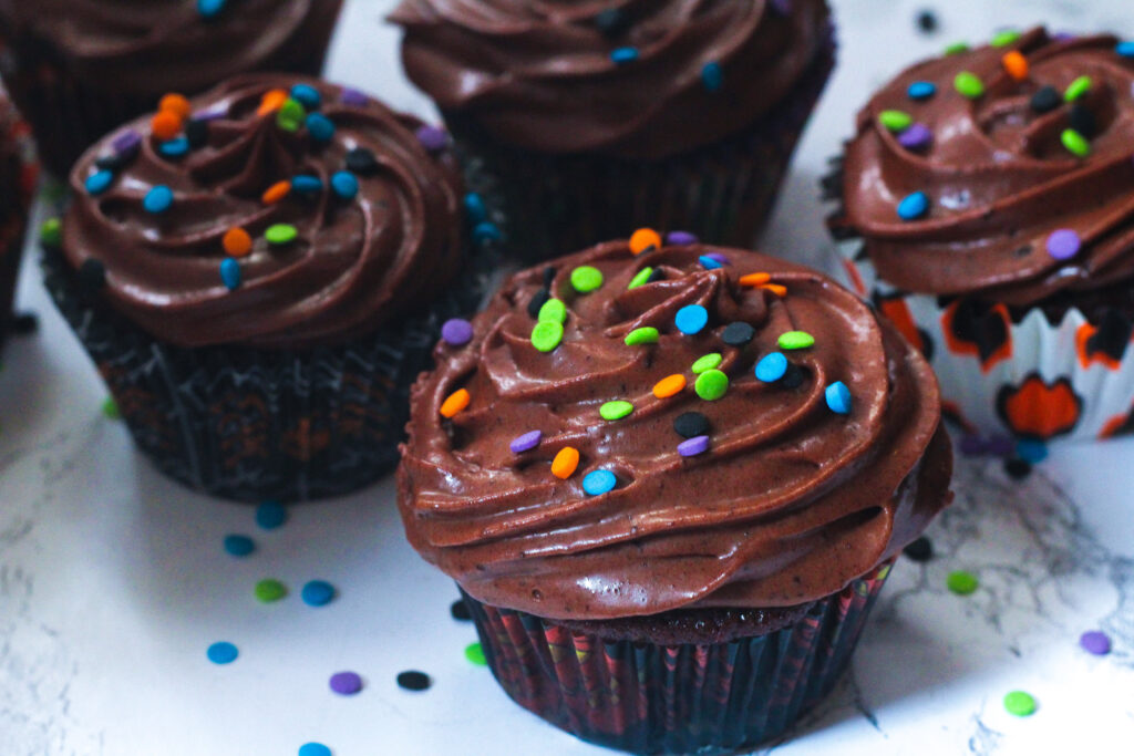 Angled view of fiery chocolate cupcakes with blue, purple, orange, and green confetti sprinkles on top, and on the white marbled surface underneath