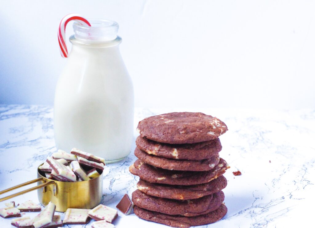 on the bottom right of the frame is a stack of fudgy peppermint chocolate cookies. to the left of the stack is a gold measuring cup overflowing with chopped peppermint bark squares. behind the measuring cup and stack of cookies is a glass jar of milk with a candy cane in it.