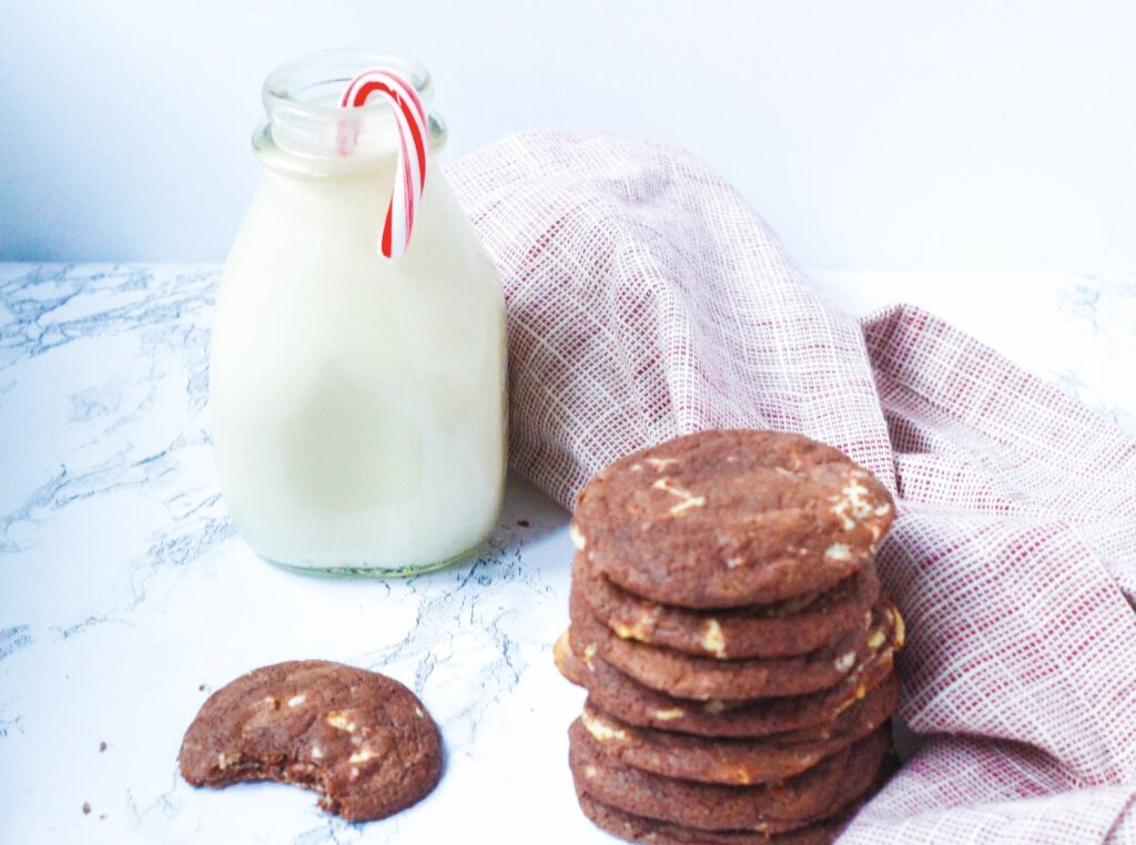 In the front right of the image is a stack of fudgy peppermint chocolate cookies.  To the right of the cookie stack is a red and white napkin that runs toward the back left of the frame where there is a glass jar of milk with a candy cane in it. In front of the milk jar and to the left of the cookie stack is a fudgy peppermint chocolate cookie with a bite taken out of it.