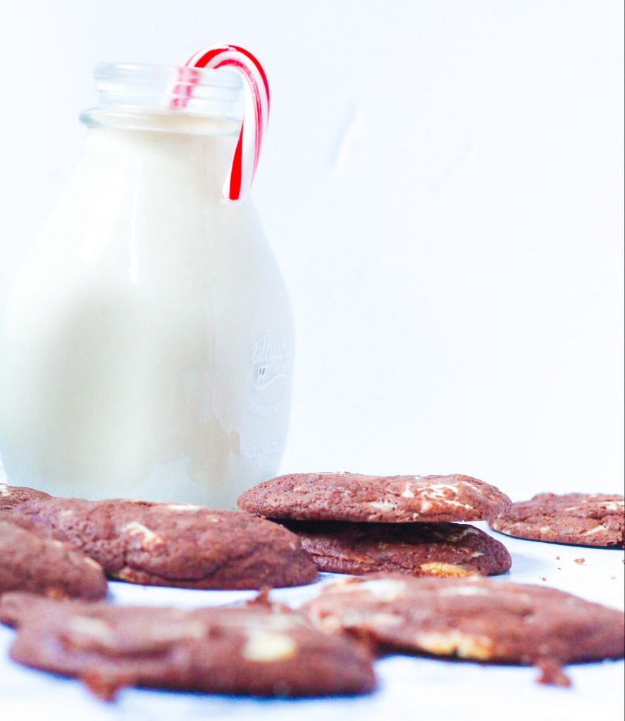 angled shot of a bunch of fudgy peppermint chocolate cookies in front of a glass jar of milk with a candy cane in it