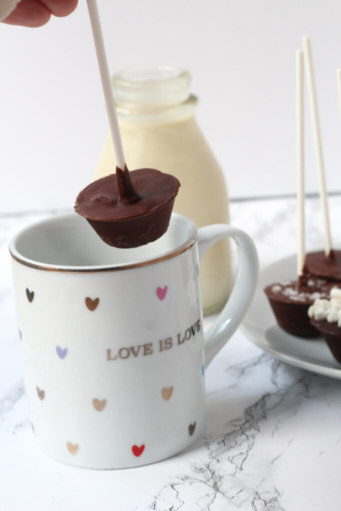 A white mug covered in multi-colored hearts that says Love is Love. Above the mug is a nutella hot chocolate on a stick about to go into the mug. The hand holding the stick is just slightly visible in the top left corner of the frame. Behind the mug is a glass jar of milk. To the right of the mug, cut off along the right side of the frame is a plate of multiple nutella hot chocolates on sticks.