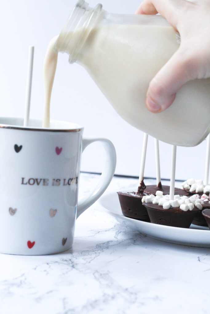 A white mug covered in multi-colored hearts that says Love is Love with a stick coming out of the top of the mug (the Nutella hot chocolate on a stick is in the mug, but you can't actually see the chocolate). coming in from the right side of the frame is a hand holding a glass jar of milk and pouring the milk into the mug. Beneath the jar on the right side of the frame is a plate of nutella hot chocolates on sticks, with the plate cut off on the right side of the frame. The most visible hot chocolate stick has mini marshmallows covering the top of the chocolate.