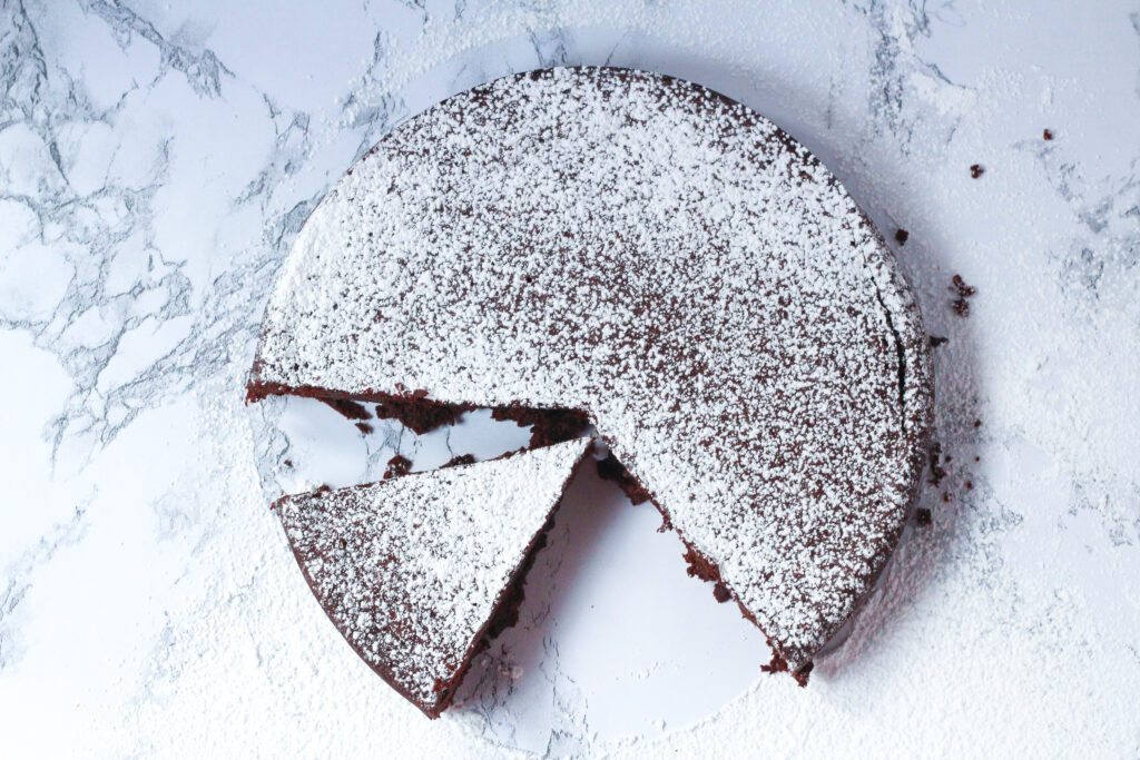 Top down view of red wine flourless chocolate cake with a few slices removed from the bottom left section of the cake. One triangular slice is sitting loosely in the open space. The cake is topped with and surrounded by a dusting of powdered sugar. The cake is sitting on a white marble surface.