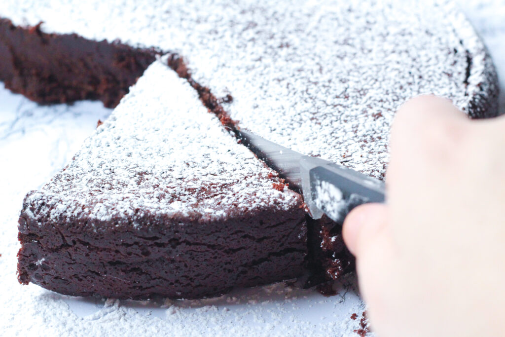 Straight on angled shot of a hand  holding a knife slicing a piece of red wine flourless chocolate cake topped with powdered sugar