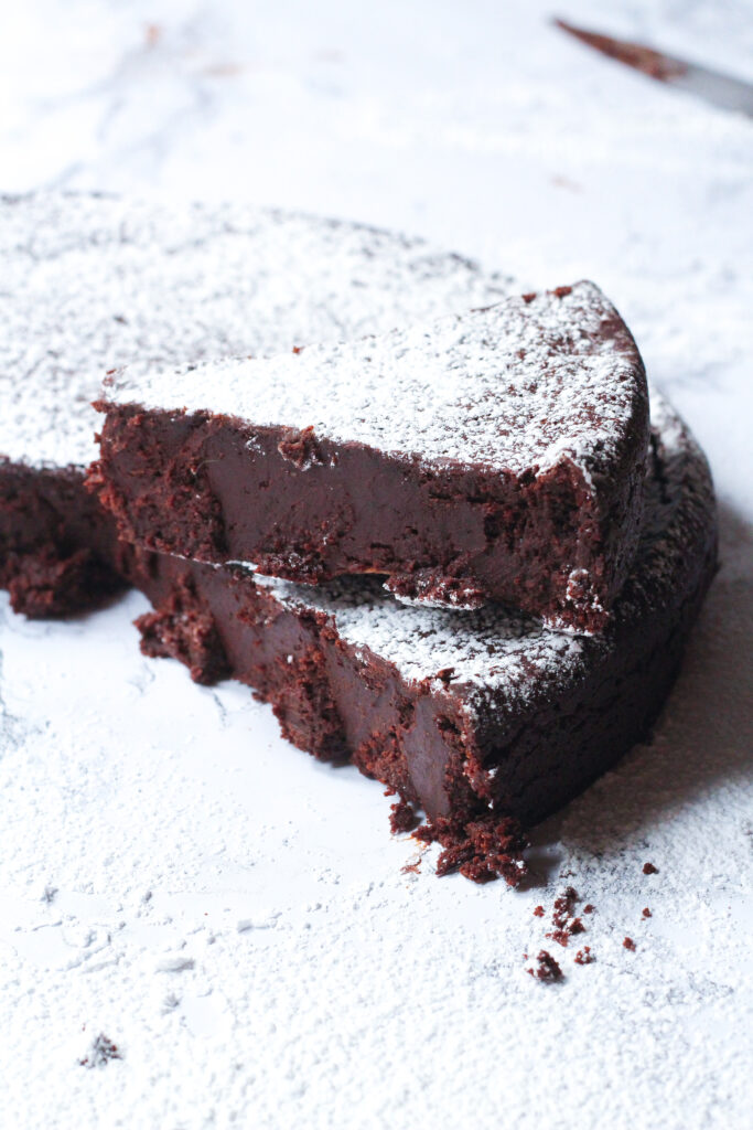 a slice of red wine flourless chocolate cake sitting on top of the remainder of the remainder of the cake from which the slice was removed, but slightly angled so that it doesn't line up exactly with the cake.  The cake and the slice are dusted with powdered sugar.