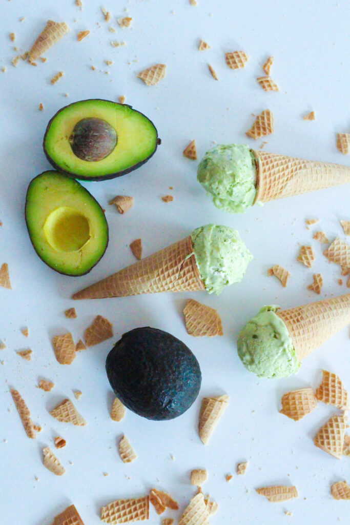 Top down view of three cones, each with one scoop of avocado ice cream on each cone. The cones are laying on their sides on a white surface, facing alternate directions. There are two halves of an avocado in the upper left corner and a whole avocado in the lower center. There are broken pieces of ice cream cones surrounding the cones and avocados.