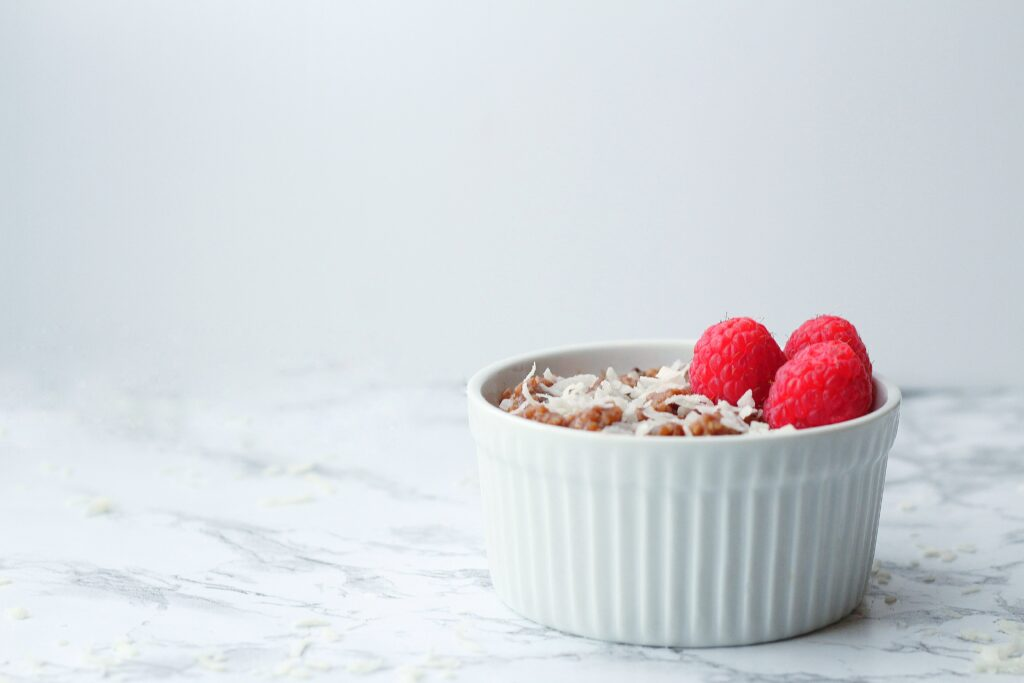 white textured ramekin of chocolate grits topped with coconut shavings and three raspberries, sitting on a marbled surface