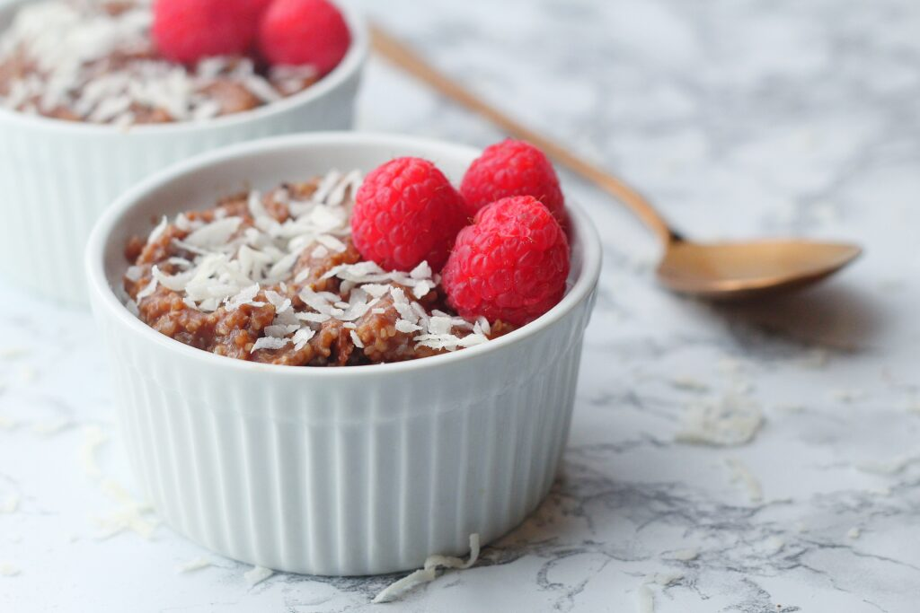 angled view of a white textured ramekin of chocolate grits topped with coconut shavings and three raspberries, sitting on a marbled surface, with a partial view of a slightly blurred second ramekin of chocolate grits in the background and a rose gold spoon laying by the ramekins in the top right portion of the photo