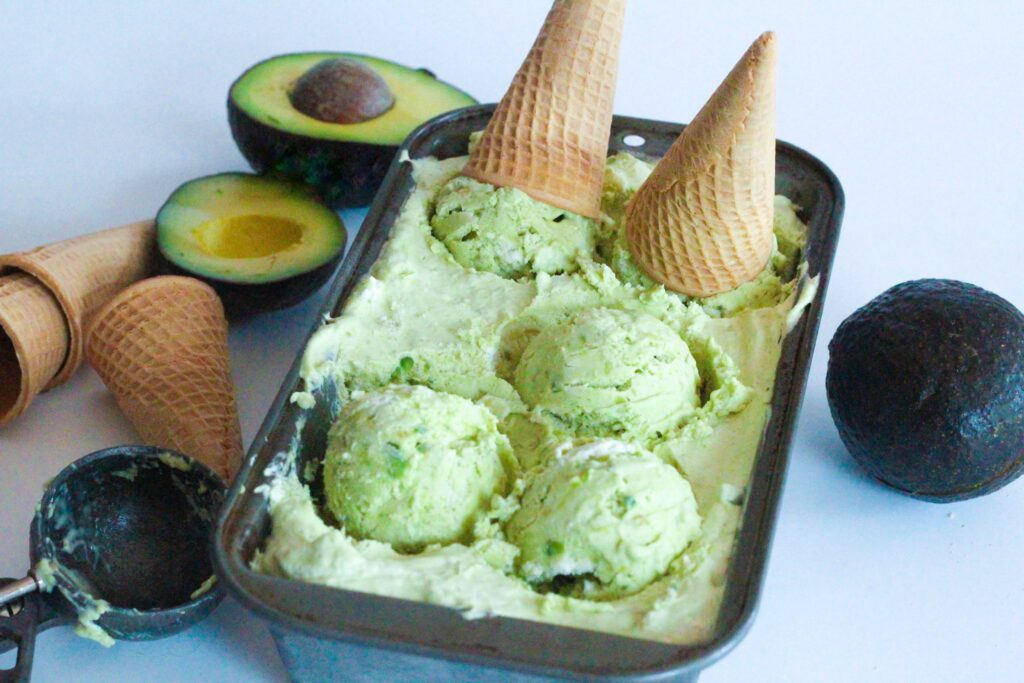 Angled view of the loaf pan of avocado ice cream with three scoops sitting in the pan, and two more with ice cream cones on them also still sitting in the pan. to the right of the pan is a whole avocado. To the left of the pan, on the upper side of the frame is two halves of an avocado, in front of them are three ice cream cones, two stacked inside of eachother, and in front of those is an ice cream scooper.
