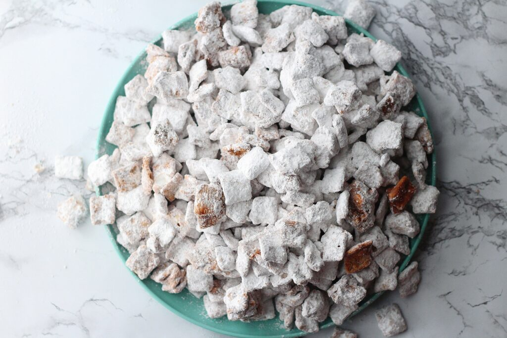 top down view of cinnamon toast crunch puppy chow on a green plate sitting on a marbled surface with some of the pieces of puppy chow overflowing off the plate onto the marble