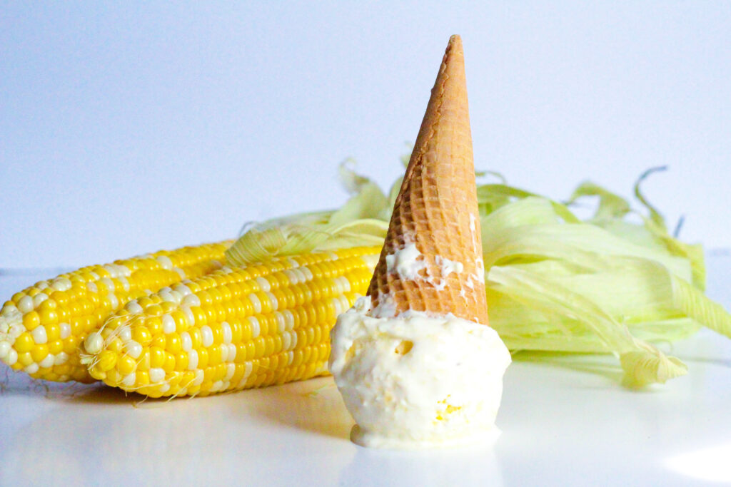 Side view of a scoop of sweet corn ice cream on a white surface with a cone going up from the scoop. Two cobs of corn are in the background.