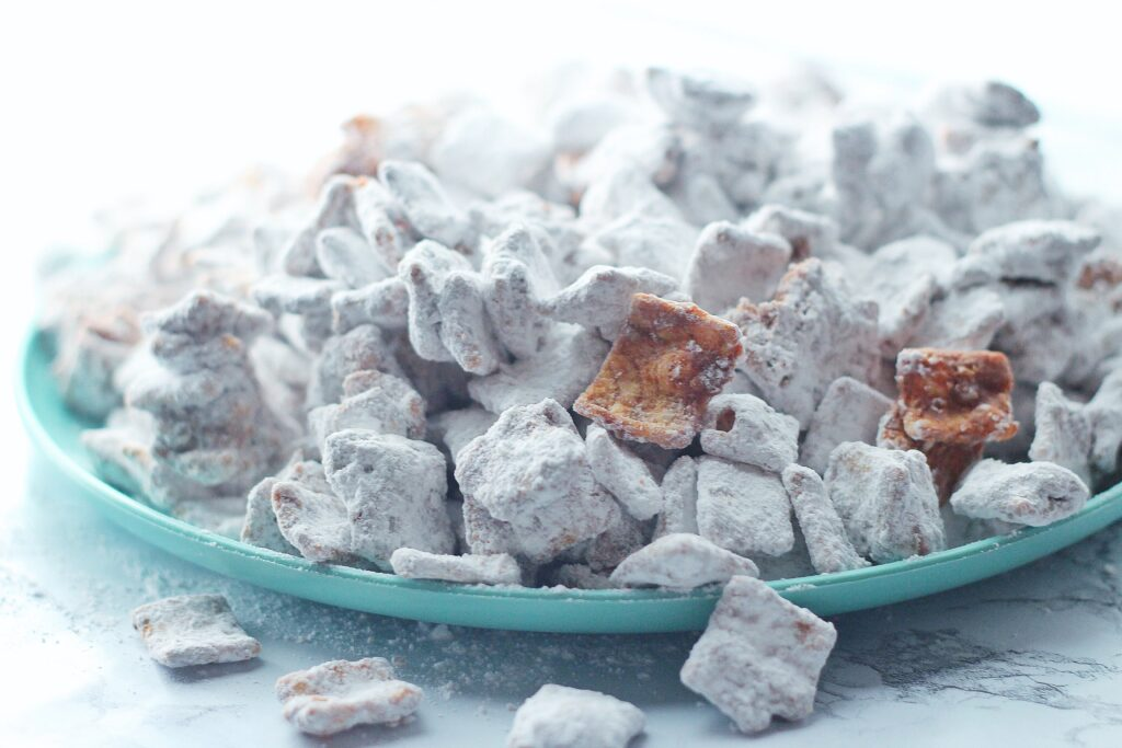 Side view of cinnamon toast crunch puppy chow on a green plate with some pieces of puppy chow falling off the plate onto a marbled surface