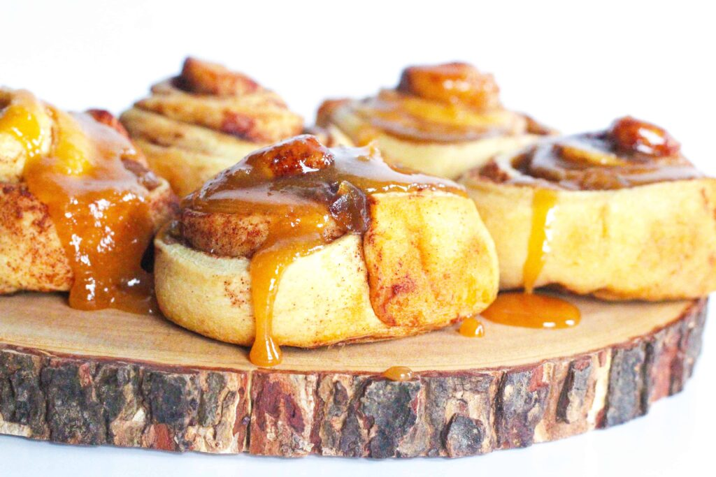 Side view of apples and honey cinnamon rolls with honey brown sugar glaze dripping