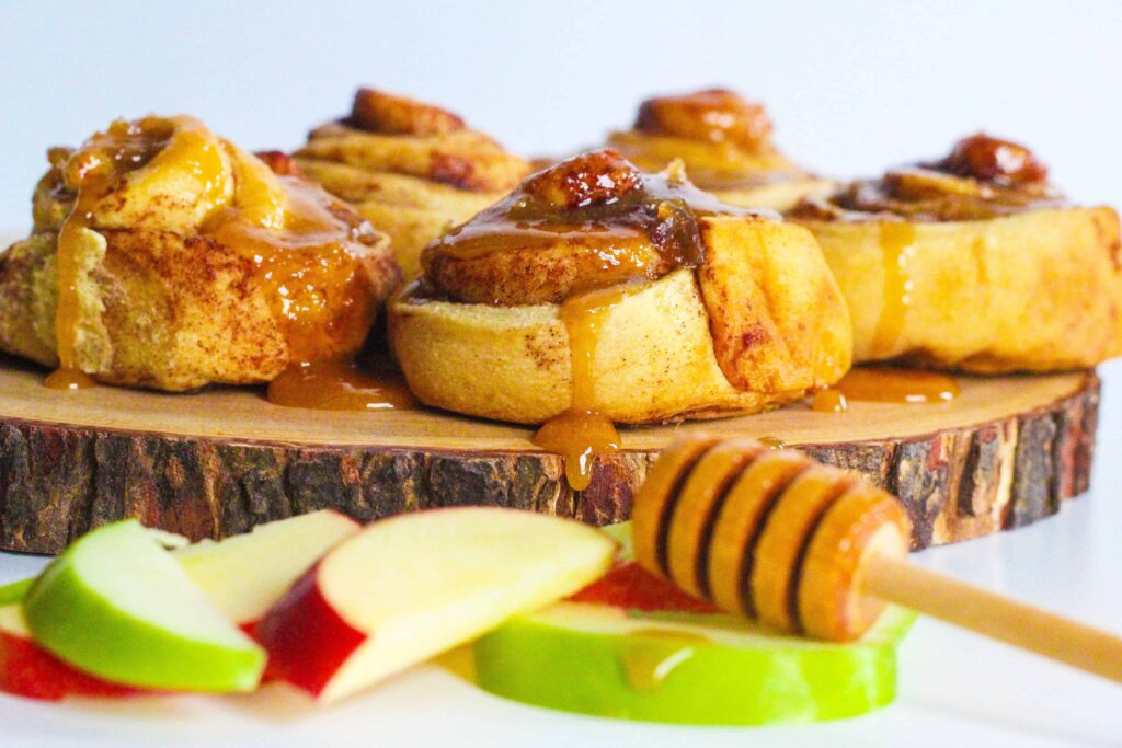 Side view of apples & honey cinnamon rolls on a round piece of wood with red and green apple slices in front of it and a honey stick resting on top