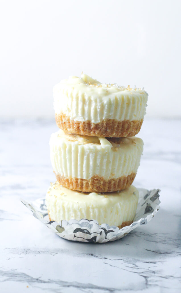 stack of three prosecco cheesecakes in an open cupcake wrapper on a marbled surface