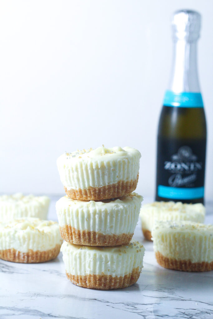 side view of a stack of 3 prosecco cheesecakes with other prosecco cheesecakes behind it and a mini bottle of prosecco in the back right of image