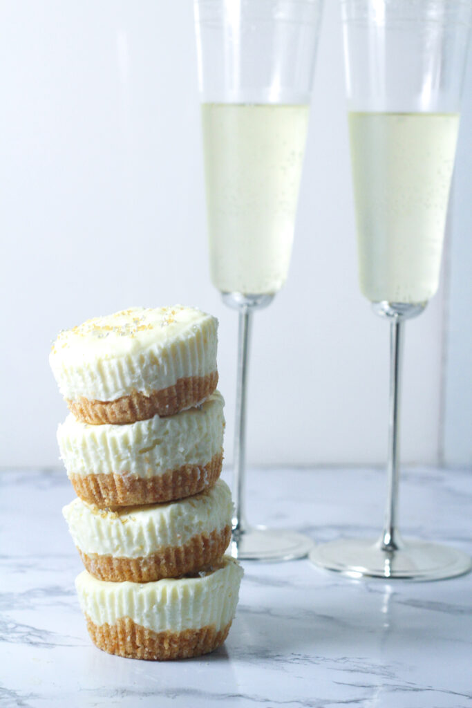 stack of 4 prosecco cheesecakes to the front left of two flutes of champagne on a marbled surface