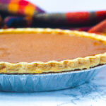Side view of a bourbon pumpkin pie slightly off to the left of the frame with a red and gold plaid scarf in the background