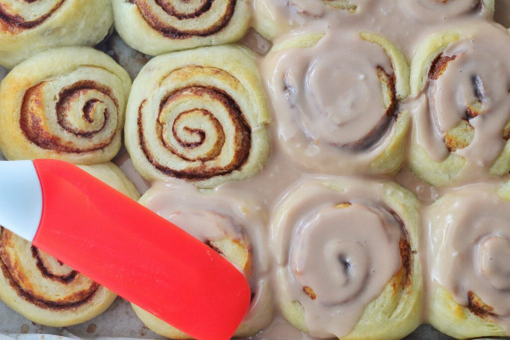 Top down view of hot cocoa rolls with those on the right hand side covered in frosting and those on the left hand side unfrosted except for one with a red spatula frosting it