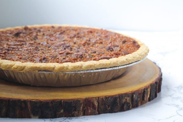 Side view of a bourbon molasses chocolate pecan pie sitting on top of a round slice of wood, all slightly off to the left of the frame