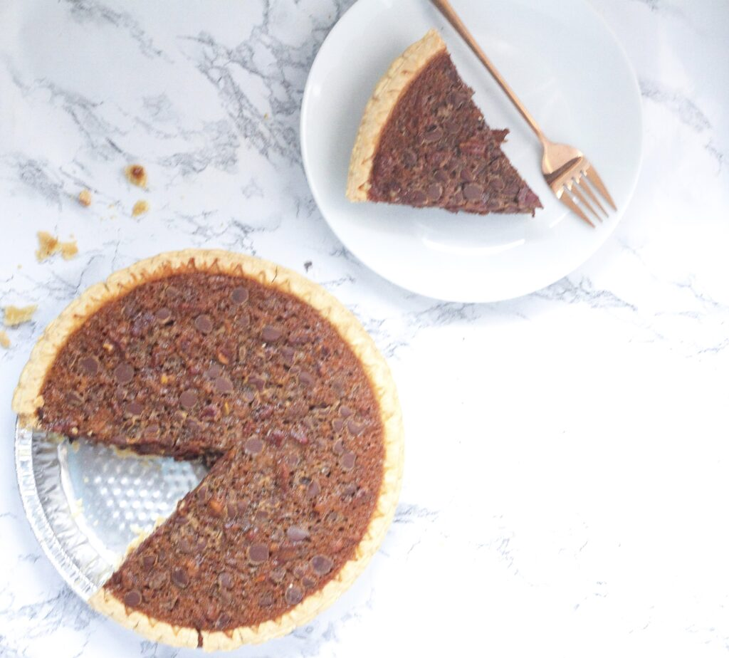 top down view of a bourbon molasses chocolate pecan pie with one slice removed in the bottom left corner of the frame, and to the top right is the slice that was removed on a white round plate with a rose gold form laying next to the slice on the plate. All on top of a white marbled surface with crumbs spread around the surface.