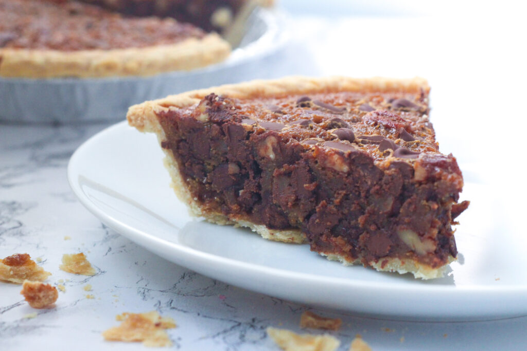 close up view of a slice of bourbon molasses chocolate pecan pie on a round white plate with crumbs around the plate, and in the background to the left there is just a bit of the rest of the pie